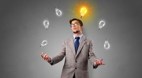 Happy person juggle with bulbs. Young business person juggle with new idea concept royalty free stock photography
