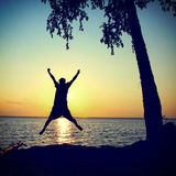 Happy Person jumping on the Sunset. Background at Seaside Stock Image