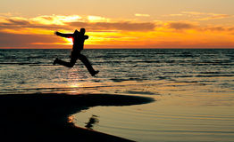 Happy person. Happy man jump on a beach at sunset royalty free stock images