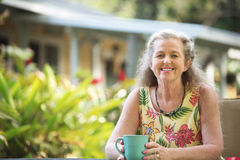 Happy Person Relaxing Outdoors. Single Caucasian adult female sitting outdoors in Maui royalty free stock photography