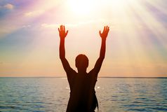 Happy person at seaside. Toned photo of a man silhouette with hands up at the sun background stock image