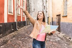 Happy person sightseeing on vacation. Tourist with map. Happy person sightseeing on vacation. Tourist with map in the city. Woman pointing at right direction or stock image