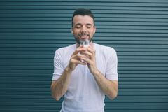 Happy person is standing and holding glass of mils. He is keeping eyes closed and enjoying the moment. Isolated on. Striped and blue background royalty free stock photo