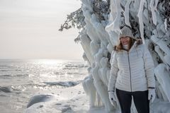 Happy person standing next to ice covered trees at Cave Point Park along Lake Michigan in winter. Woman stnading next to ice covered tree along Lake Michigan at royalty free stock photo