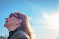 Happy person walking outside in spring. Happy woman walking in park looking up on bright sunny day stock photo