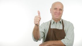 Happy Person Wearing Kitchen Apron Thumbs Up Good Job Sign.  royalty free stock photo