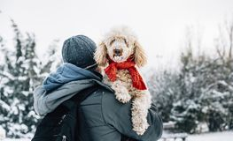 Happy pet and his owner having fun in the snow in winter holiday season. Winter holiday emotion. Man holding cute puddle dog with red scarf. Film filter image stock photos