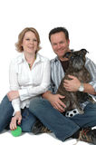 Happy Pet Owners. Happy married couple and their dog. Family portrait with a pet Royalty Free Stock Photo