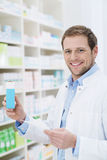 Happy pharmacist holding a blank box of medication Stock Image
