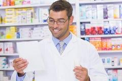Happy pharmacist looking at prescription Stock Photo