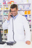 Happy pharmacist on the phone Stock Photo