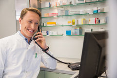Happy pharmacist on the phone using computer Stock Photography