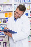 Happy pharmacist on the phone Royalty Free Stock Image