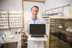 Happy pharmacist showing laptop screen. At the hospital pharmacy royalty free stock image