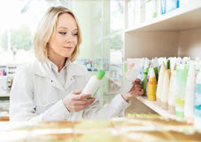 Happy pharmacist woman in pharmacy shop Royalty Free Stock Images