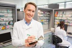 Happy pharmacist writing on clipboard. At the hospital pharmacy Stock Photos