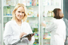 Happy Pharmacy chemist woman in drugstore royalty free stock photography