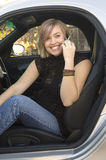 Happy phone call. Happy blond teen using cell phone sitting in sports car Royalty Free Stock Image