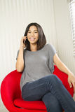 Happy phone call. A happy woman sitting in a red chair talking on a phone Royalty Free Stock Image