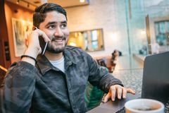 Happy phone chatting man in cafe with computer. Freelancer employed out office workplace. Big city lifestyle Royalty Free Stock Photography