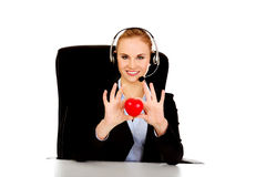 Happy phone operator woman holding heart toy Royalty Free Stock Image