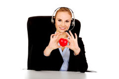 Happy phone operator woman holding heart toy Royalty Free Stock Photo