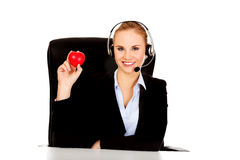 Happy phone operator woman holding heart toy Royalty Free Stock Photos