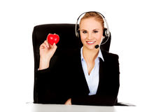 Happy phone operator woman holding heart toy Royalty Free Stock Images