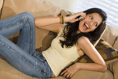 Happy Phonecall. A beautiful young Hispanic woman laying on a settee and enjoying a call on her mobile phone Stock Photography