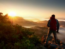 Happy photo enthusiast enjoy photography of fall daybreak in nature on cliff. On rock. Dreamy fogy landscape, misty sunrise in a beautiful valley below stock image