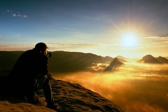 Happy photo enthusiast is enjoying fantastic miracle of nature on cliff on rock. Dreamy fogy landscape bellow. Happy photo enthusiast is enjoying fantastic stock photography