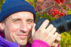 Happy photographer on arrowwood bush background Stock Photo