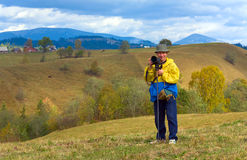 Happy photographer on autumn mountain background Royalty Free Stock Photography