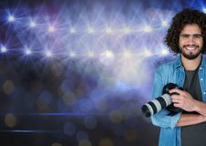 Happy photographer in front of stadium lights with blurred lights Royalty Free Stock Photography