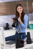 Happy photographer girl at work. Holding camera, smiling Royalty Free Stock Photo