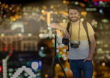 happy photographer rest on tripod in front of the city at night ( with blurred lights) and bokeh ove Stock Photo