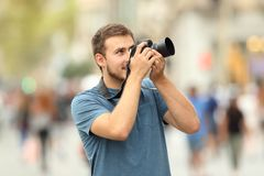 Photographer taking photos on the street with a dslr camera. Happy photographer taking photos on the street with a dslr camera Royalty Free Stock Photography