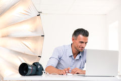 Happy photographer using laptop Royalty Free Stock Images