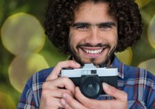 happy photographer with vintage camera. Green and yellow blurred lights background royalty free stock photos