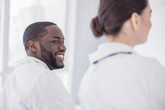 Happy physician hearing report in hospital office. Focus on smiling bearded african medical adviser listening lecture while sitting near female colleague in Stock Photography