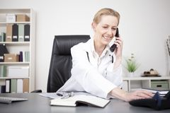 Happy Physician Leaning on Table While on Phone Royalty Free Stock Image