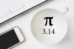 Happy Pi Day, written in black pen on white. On the desk a laptop, a cup, a hand holds the phone royalty free stock photo