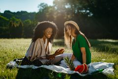 Happy picnic of two multi-race girl friends sitting on the plaid on the meadow.The attractive young african girl with royalty free stock photo