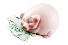 Happy piggybank on heap of euros Royalty Free Stock Photo