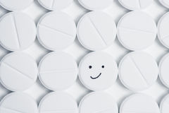 Happy pill surrounded by white prescription pills Royalty Free Stock Image