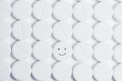 Happy pill surrounded by white prescription pills Royalty Free Stock Images