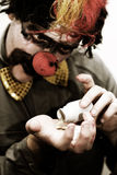 Happy Pills. Sad Clown Desperately Pours Out Happy Pills Into His Hand To Help Cure His Sorrow Royalty Free Stock Image