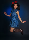 Happy pin-up girl jumping. Happy jumping pin-up girl in blue dress stock image