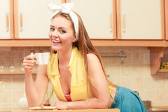 Happy pin up girl drinking tea or coffee at home. Royalty Free Stock Image