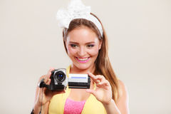 Happy pin up girl woman filming with camcorder. Happy smiling pretty pin up girl filming with camcorder. Attractive gorgeous young retro woman Stock Photography